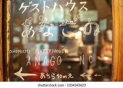 ONOMICHI, JAPAN - MARCH 25, 2017 : A sign drawn by hand on the window of 'Akubi Cafe', directing the way to 'Onomichi Guesthouse Anago no Nedoko', taken in the middle of Onomichi Shopping Arcade.