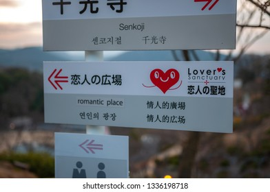 ONOMICHI, JAPAN - MARCH 25, 2017 : An interesting direction sign with one that leads to 'romantic place' which is actually a Lover's Sanctuary that has a sculpture of two loving cats in Senkoji Park.