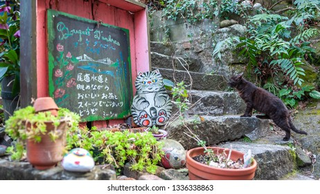 """ONOMICHI, JAPAN - MARCH 25, 2017 : A black cat looking at a cut-out drawing of a cat on a narrow street on the slopes of Mt. Senkoji's Onomichi Cat Alley, or also known as """"Neko no Hosomichi""""."""