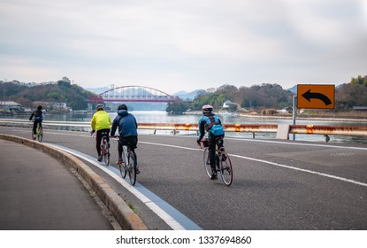 ONOMICHI, JAPAN - MARCH 26, 2017 : Cyclists riding at Mukoujima Island which is the starting point of the Shimanami Kaido, with a red-colored bridge called 'Mukaishimao Bridge' in the distance.