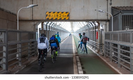 ONOMICHI, JAPAN - MARCH 26, 2017 : Cyclists riding on a bike path that runs under the Innoshima Bridge which connects Mukoujima Island and Innoshima Island as part of the Shimanami Kaido adventure.