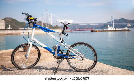 ONOMICHI, JAPAN - MARCH 26, 2017 : A mini velo bike used for the Shimanami Kaido with Innoshima Bridge in the background which connects Mukoujima Island and Innoshima Island in the Shikoku Region.
