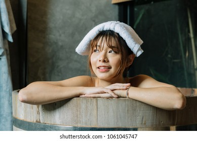 Onsen series: Asian woman relaxing in wooden bathtub