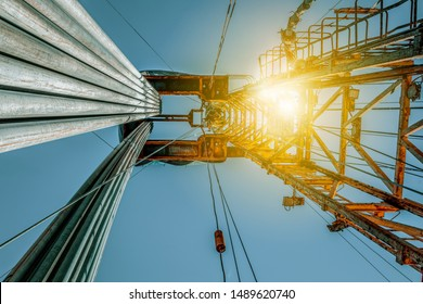 Onshore land rig in oil and gas industry. Oil drilling rig against a blue sky with clouds.