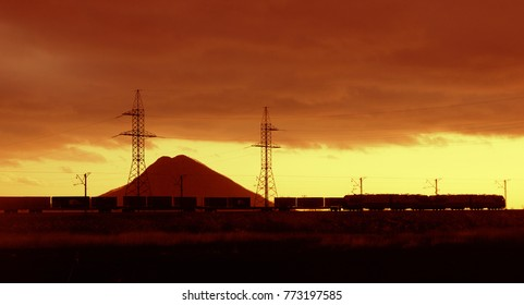 ontainer train is racing at sunset against the background of a mountain and towers with wires