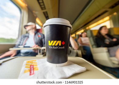 Ontario, Canada - 24 June 2017: Interior of railcar on a ViaRail train on its way to Toronto, with a Via Rail Paper Coffee Cup in foreground