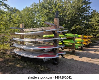 Ontario, Canada - Aug 02, 2019: Many paddle boards, kayaks and canoes  stacked on a rack at a sandy beach. Sunny day, Ontario, Canada. Water sports and activities concept.