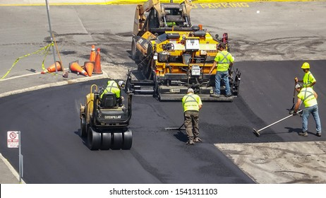 ONTARIO CANADA - JULY 31 2019: Industrial pavement truck laying fresh asphalt and a small drum roller paving fresh asphalt with road workers in a paving construction project