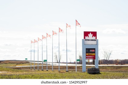 Ontario, Canada Oct 2019 - Petro Canada sign with prices at Canadian gas station (this petrol station is a Suncor energy brand) with Canadian flags waving.