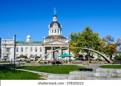 Ontario  Canada - October 19th, 2008 :  tourists sit on a bench in front of city Hall of Kingston and Confederation arch fountain,  Ontario  Canada