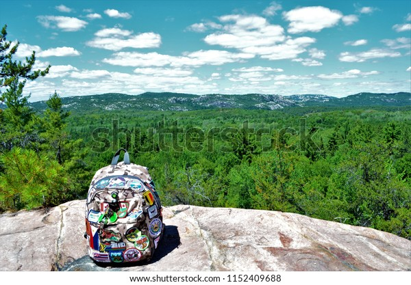 Ontario, Canada on July 18, 2018.  The traveller's backback with all the badges collected from all the hiking places in the world, sitting on a rock in Killarney Ontario.