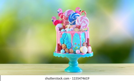 On-trend candyland fantasy drip cake for children's, teen's birthday, anniverary, mother's day and valentine's day celebrations, against bokeh garden background.