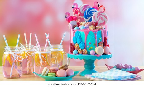 On-trend candyland fantasy drip cake for children's, teen's birthday, anniverary, mother's day and valentine's day celebrations. in party table setting with mason jars pink lemonade.