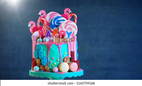 On-trend candyland fantasy drip cake with gift in birthday party setting.