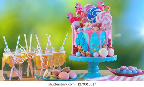 On-trend candyland fantasy drip cake with pink lemonade in garden party setting.