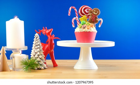 On-trend candyland festive Christmas cupcakes on blue background.