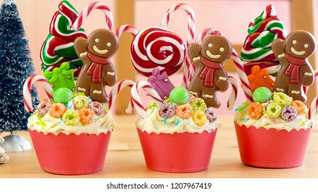 On-trend candyland festive Christmas cupcakes in colorful party table setting.