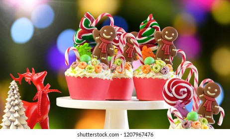 On-trend candyland festive Christmas cupcakes against bokeh lights background.