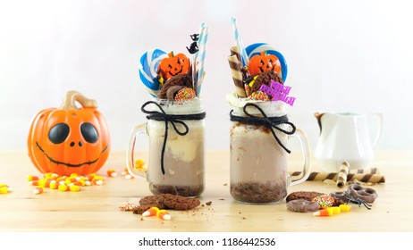 On-trend Happy Halloween theme freak shakes chocolate milkshakes decorated with candy, cookies and lollipops.