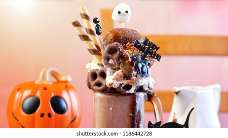 On-trend Happy Halloween theme sweet and salty chocolate freak shakes milkshakes decorated with candy, pretzels and donuts.
