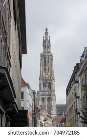 Onze Lieve Vrouwekathedraal (Cathedral of Our Lady) in Antwerp Belgium at the end of the street. Shops line the high street with the cathedral of Antwerp at the end of the street. Tall gothic tower.