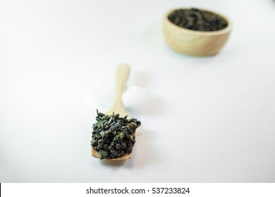 Oolong tea in wood bowl on white background.