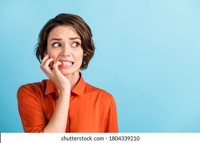 Oops. Closeup photo of sad terrified lady horrified facial expression made big mistake feel guilty look side empty space bite lips fingers wear orange shirt isolated blue color background