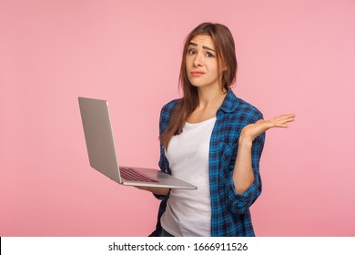 Oops, it doesn't work! Frustrated girl in checkered shirt holding laptop and raising hand in helpless gesture, worried about software bug, program error. indoor studio shot isolated on pink background