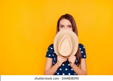 Oops, it is not me. Charming, pretty girl in polka-dot t-shirt close her half face with hat, looking with mad eyes, hiding from someone, watching something, isolated on yellow background