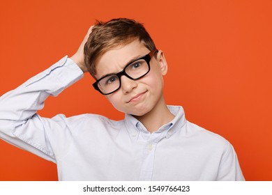 Oops, some problems. Doubtful teenage boy in glasses scratching his head, orange background