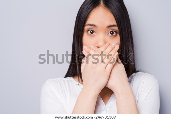 Oops! Surprised young Asian woman covering mouth with hands and staring at camera while standing against grey background