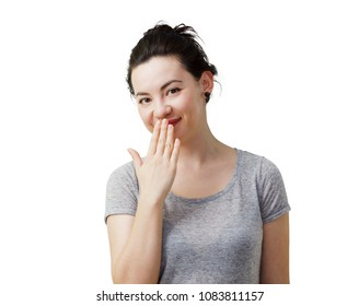Oops! Surprised young mixed caucasian-asian race woman covering mouth with hand and staring at camera. Isolated on white.