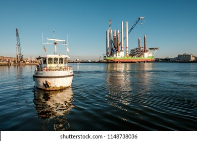 Oostende, Belgium - 2 August 2018: Passenger ferry in the port of Ostend with in the background the mighty wind turbine installation vessel 'Sea Installer'