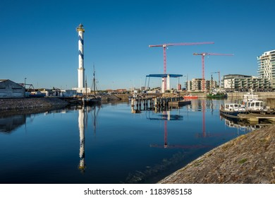Oostende, Belgium - 2 August 2018: Old lighthouse of Ostend known as 'Lange Nelle', reflected in a commercial dock.