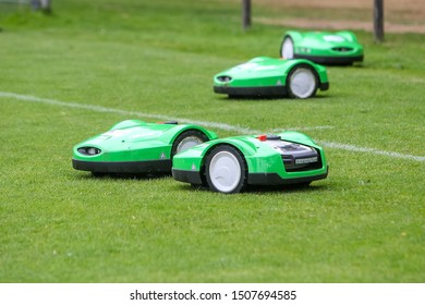 Oosterbeek, Netherlands - July 11, 2018: Automatic robotic lawnmower on green grass in the stadium. Mowing the lawn with a robot.
