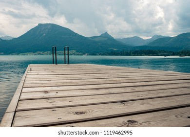ootbridge with a pool ladder in the lake in Austria which wolfgangsee is called with mountains in the background