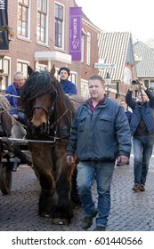 OOTMARSUM, NETHERLANDS -MARCH 26, 2016. Man escort wagon with horses for getting wood at Easter fire.