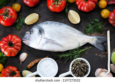 op view of fresh sea food on grunge textured black background. Shrimps, bream, herbs, lemon