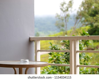 open air balcony terrace of a mountain resort hotel with metal fence minimal coffee table with empty glass ashtray
