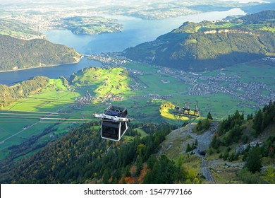 An open air cable car on Stanserhorn, Switzerland with lake Luzern in the background.