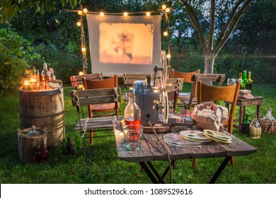 Open air cinema with retro projector in summer garden