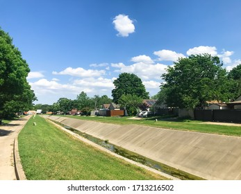 Open air drainage canal at residential neighborhood in suburbs Dallas, Texas, America. Back alley with suburban houses under cloud blue sky.