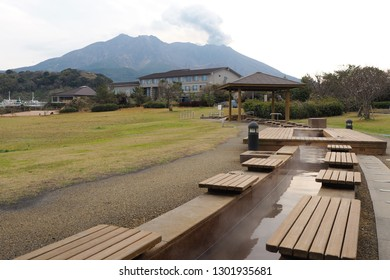 Open air foot bath in southern Kyushu, Japan near Kagoshima with the smoking volcano Mt. Sakurajima behind. No wonder where the how water for the foot bath is coming from.