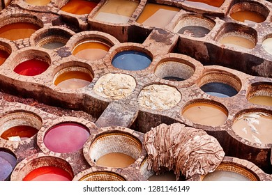 The open air historic Chouara leather tannery in Fes, Morocco is filled with stone vats containing dyes and animal hides that are being colored.