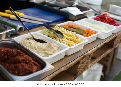 open air kitchen products for cooking falafel in dishes on a wooden table. Street food ready to serve on a food stall.