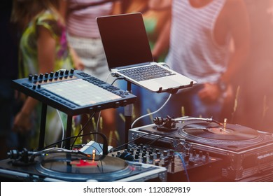 Open air music festival stage equipiment.DJ setup for playing music set on dance party.People dancing on background at backyard party.Disc jockey setup with midi controller & vinyl records player