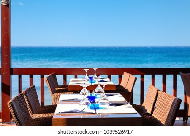 The open air restaurant by the sea is ready to receive visitors. Greece.