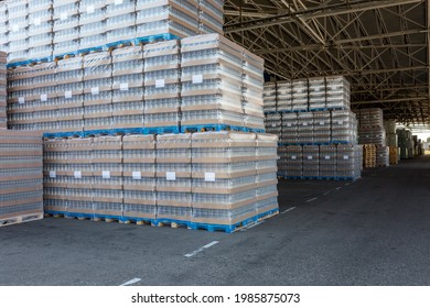 Die Lagerung und Beförderung des Fertigerzeugnisses im Freien in der Industrie. Klarglasflaschen für alkoholische oder alkoholfreie Getränke und Konservengläser, die auf Paletten für Gabelstapler gestapelt sind.