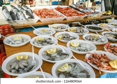 Open air street food fish market on Bari promenade with raw fresh sushi ready to eat: shrimp, oyster, sea urchin, cuttlefish, squid, octopus and salpa, sole and various fish
