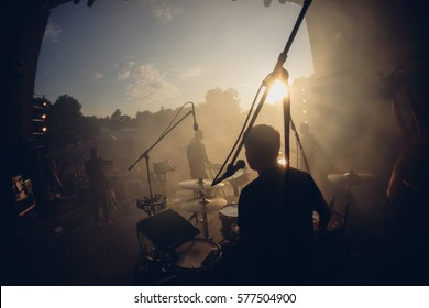 Open air view from the stage to the drummer and another band mates in sunset warm lights. Stage smoke, sun rays in it. Silhouettes of the summer festival